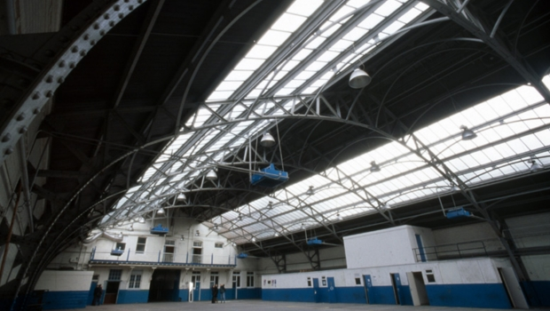 Image depicts an empty Drill Hall before the studios were built and flooring laid down.