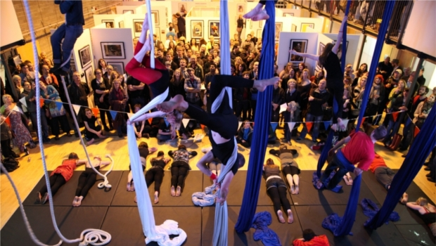 Aerial artists perform in front of a busy crowd at a Stevenson College photography exhibition.