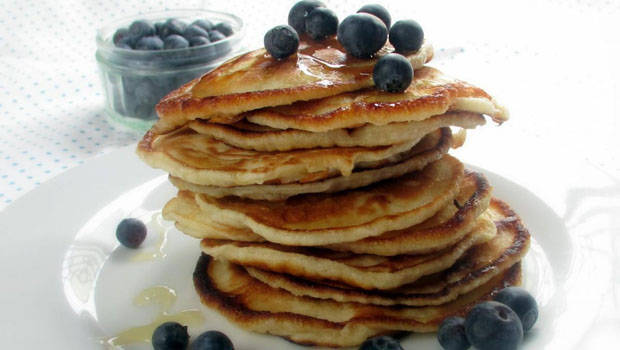Blueberry pancakes stacked on a plate.