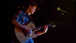 Musician Tomlin Leckie plays guitar on stage.