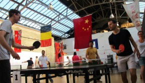 Table tennis players compete in The Out of the Blue Drill Hall underneath various flags of the world.