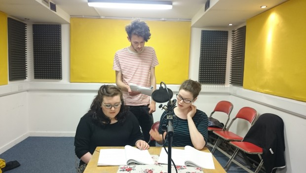 Three young Actors rehearse dialogue from a radio play performance in The Out of the Blue Drill Hall's Music Room.