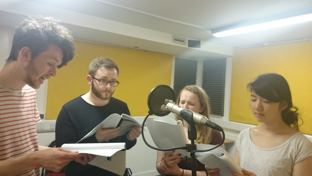 Four young Actors rehearse dialogue from a radio play performance in The Out of the Blue Drill Hall's Music Room.