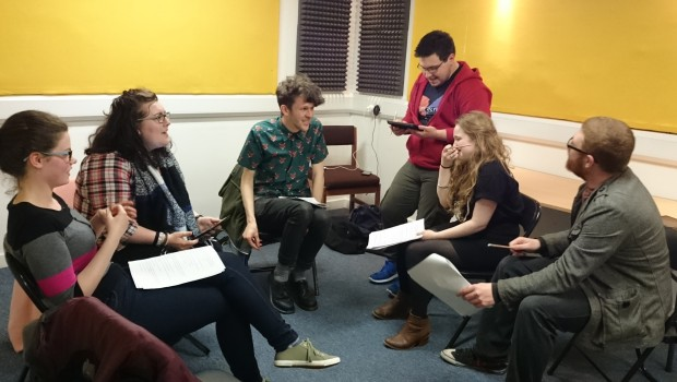 Six young Actors discuss the script at a radio play performance in The Out of the Blue Drill Hall's Music Room.