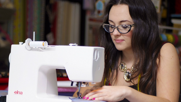 A woman uses a sewing machine at a 'Sew Confidence' class