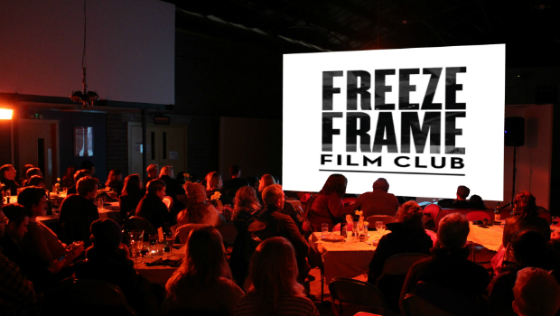 A group of people look at a cinema screen at a Freeze Frame Film Club night