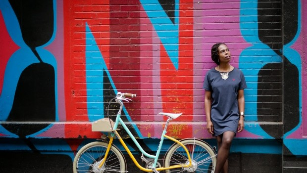Jools Walker leans against a brightly coloured wall with a bicycle