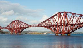 The Forth Rail Bridge is captured with a blue sky behind it.