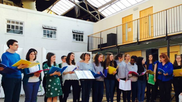 A large choir passionately sings in the main space of the Drill Hall