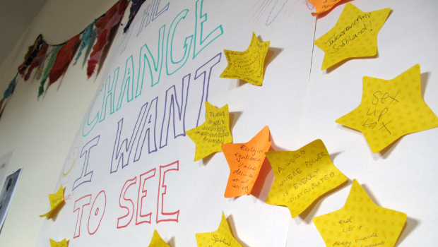 "Sticky notes with ideas fill the wall of a poster that reads ""Change I Want to See"""