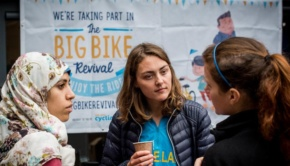 Three women talking about cycling in front of a 'Big Bike Revival' poster.