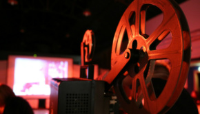 A movie projector plays a reel of film onto a cinema screen at a previous Screen Bandita event in the Drill Hall