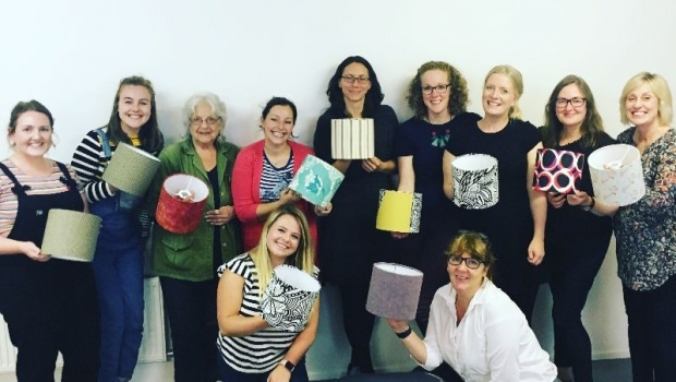 A group of women holding their created lampshades