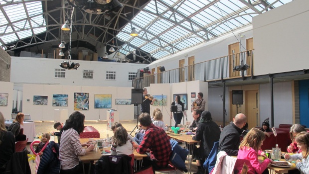 The Drill Hall with people in the cafe, live music and an exhibition in the background