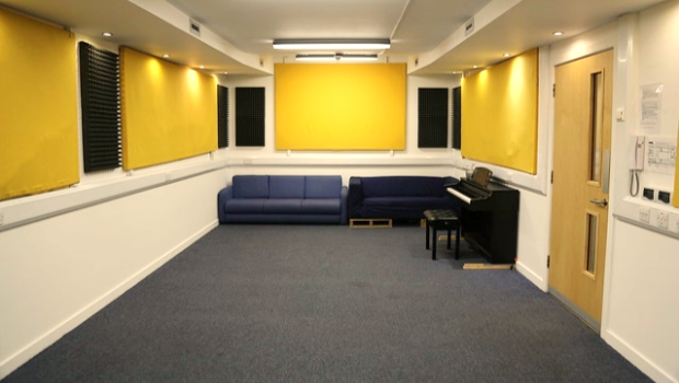 The Drill Hall Music Room, Edinburgh with a piano and two sofas
