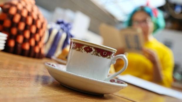 A cup of tea and a woman reading a book at the Drill Hall Arts Cafe