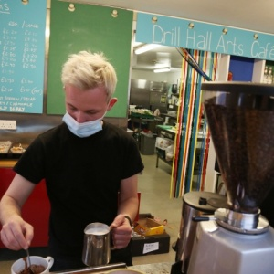 Cafe staff member making coffee in cafe